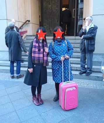 ベルリンのオペラ座前にて。青い水玉のコートにピンクのスーツケースを持ったAさんと、Aki