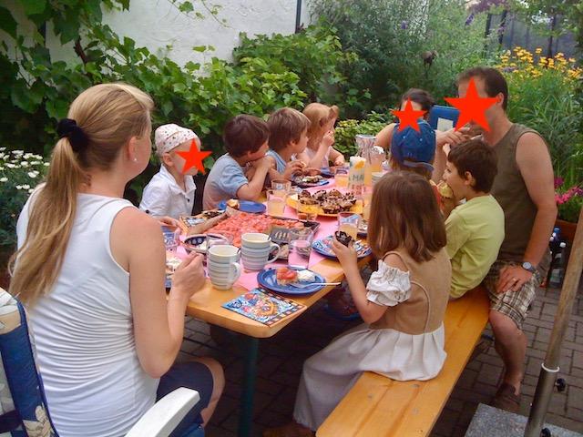 中庭のテーブルを囲む子ども達と、大人3人