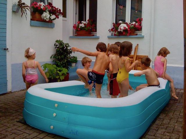 窓の前に置かれた大きなビニールプールで遊ぶ子ども8人