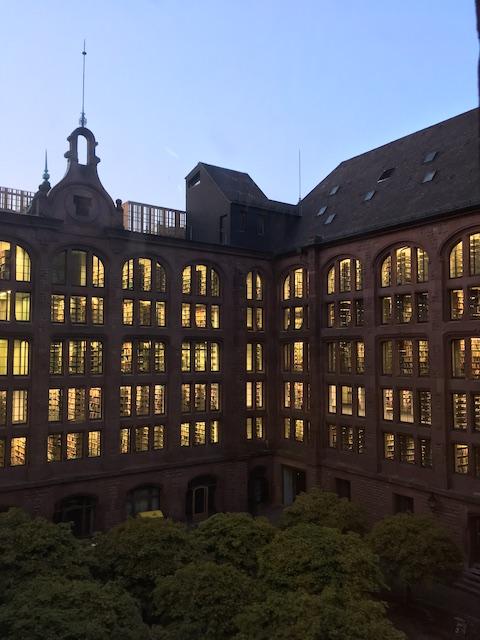 日暮れの時間帯、窓から書架が見える煉瓦造りの建物