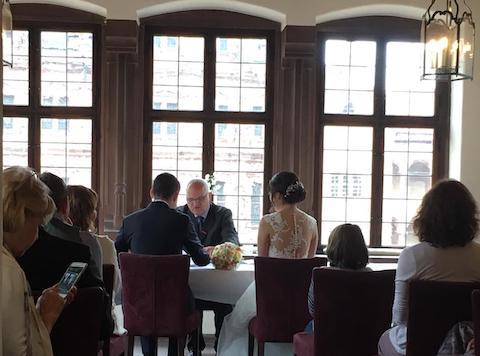 テーブルに向かっている新郎新婦と、役所の男性