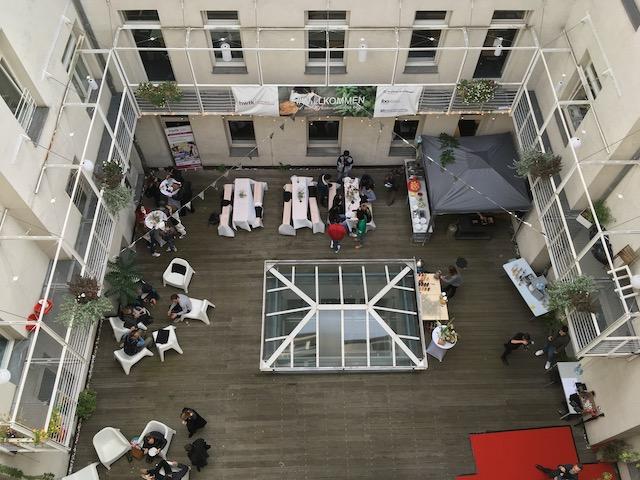 建物の中庭に並べられたテーブル&椅子と、食事する人々