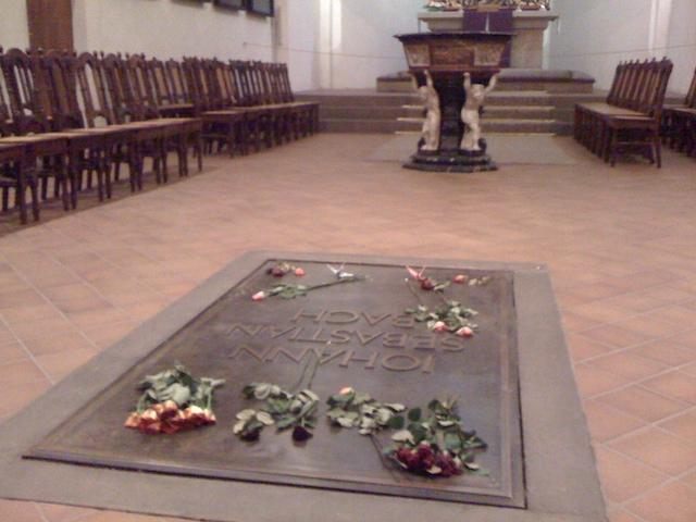 教会の祭壇前の床にある、バッハのプレートと、供えられた花