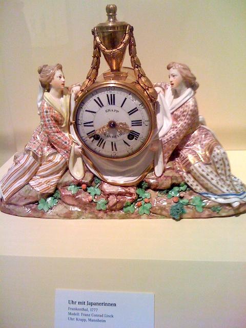 置き時計にもたれている陶器の女性2人