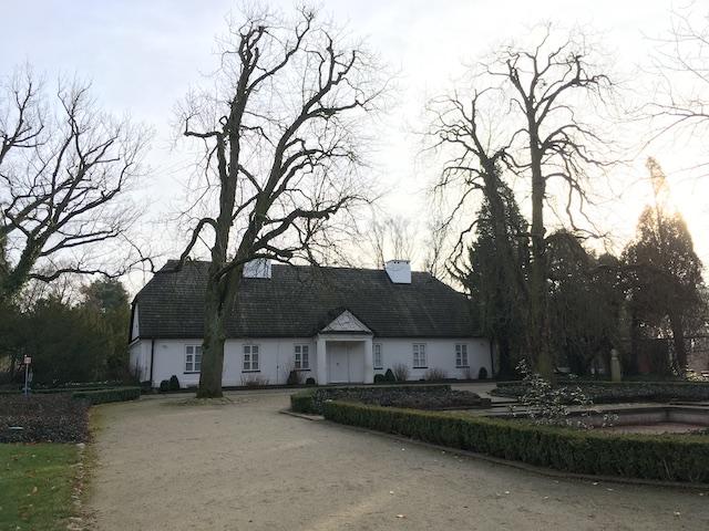 大きな庭の中にある白い平屋