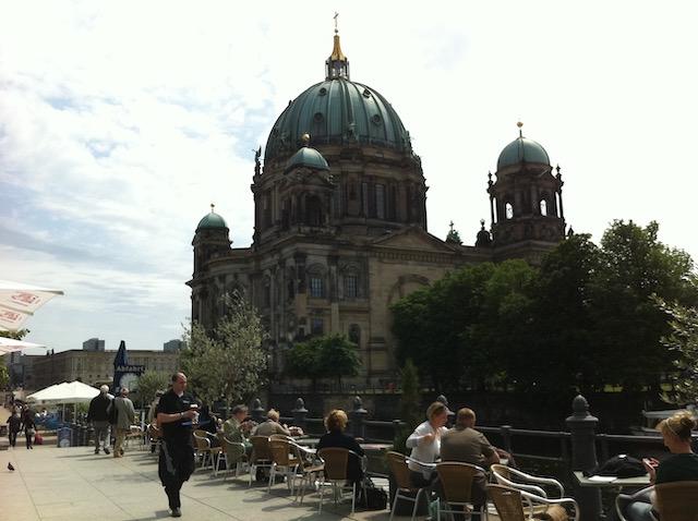 重厚な大聖堂の対岸、テラス席で食事を楽しむ人々