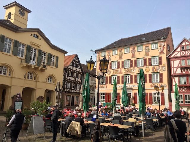 木組みの可愛らしい建物が並ぶ広場で、賑わうレストランのテラス席