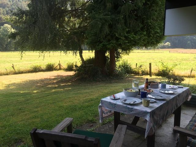 草原と、庭のテラスに置かれたテーブルの上の食事