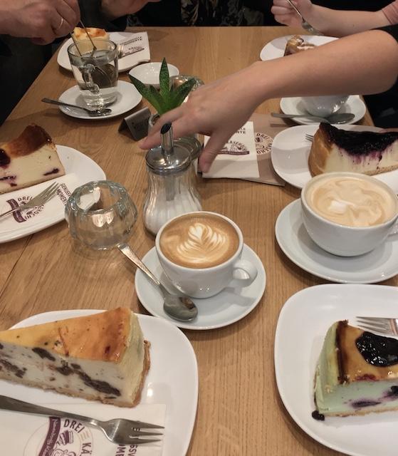 テーブルの上に並んだ様々な種類のチーズケーキとドリンク