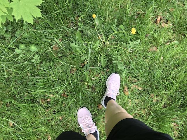 ピンクのシューズを履いた足下と、鮮やかな色の緑地