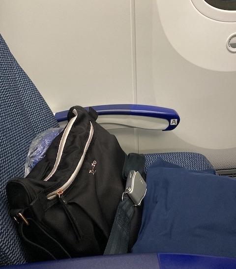 安全ベルトをされた、椅子の上の黒いショルダーバッグ