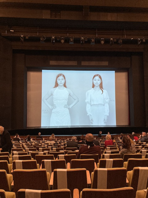 空いている座席と、舞台のスクリーンに映された日本人ダンサー2人の写真