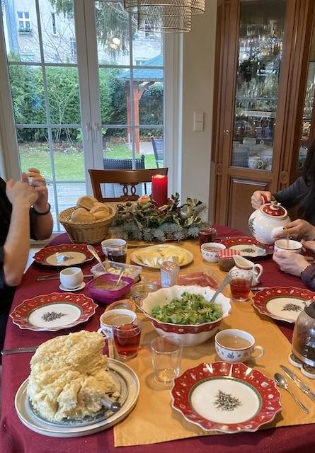 ロウソクの飾り、クリスマス柄の食器と、様々な食べ物が並ぶ華やかなテーブル