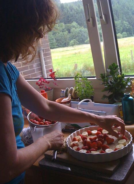 キッチンでタルト型にいちごを並べている女性。窓の外には草原が広がる