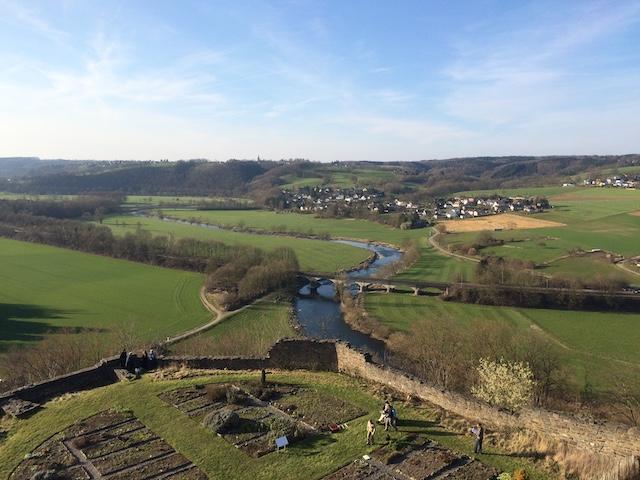 低い丘と緑地が連なる中に川が流れ、橋が掛かっている