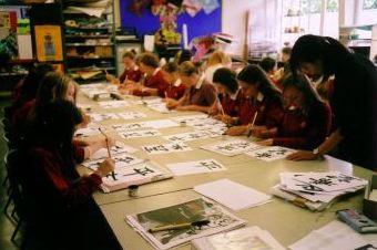 長机に並んで習字の練習をしているイギリス人の生徒たち