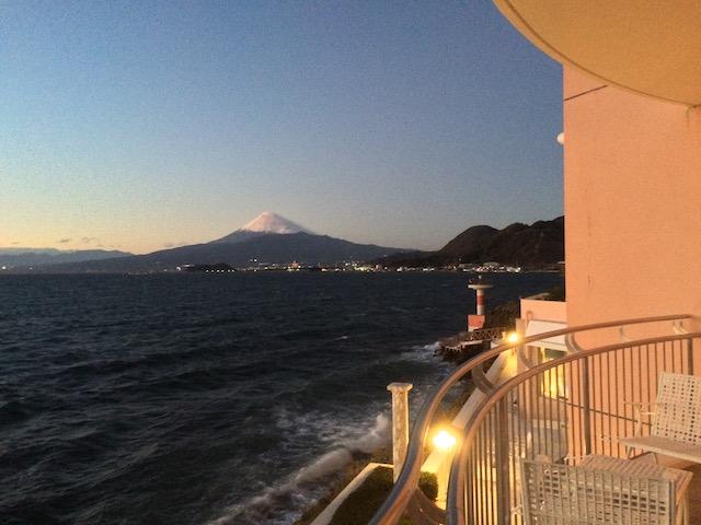 夕闇が迫る中で、海の向こうに浮かび上がる富士山