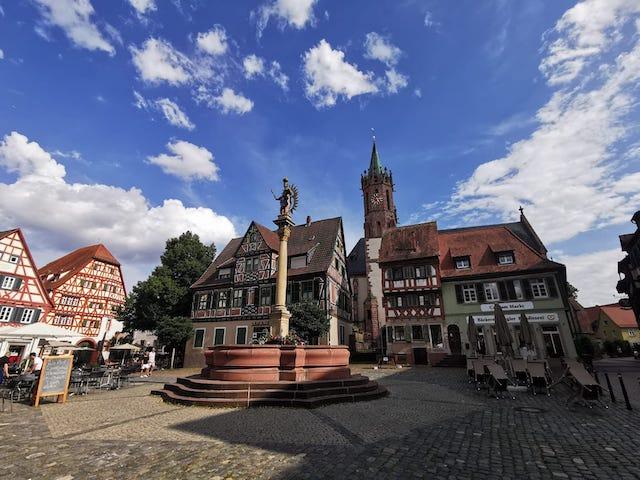 真ん中に背の高い像があり、周りに可愛い建物が並んだ広広場
