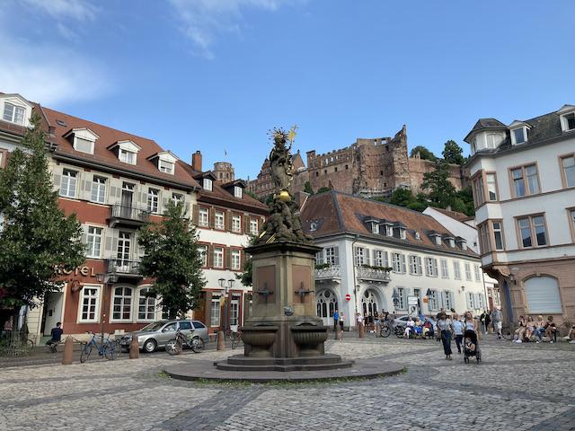 石像が立つ石畳の広場、背景にはハイデルベルク城が見える
