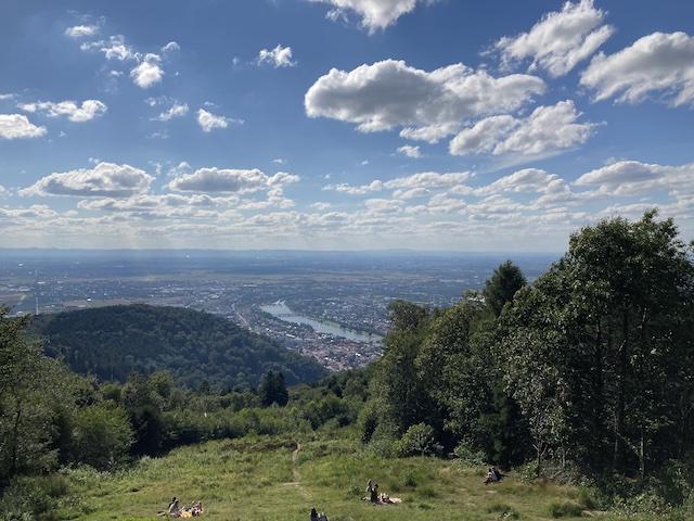 草の上に座って、雲が浮かぶ青空の下に広がる風景を眼下に眺めている人々
