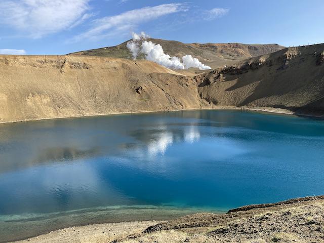 クレーターに溜まった真っ青な水、奥には煙が見える