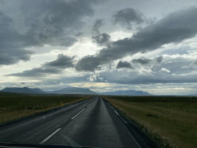 遠方に山が見える平らな道路の上、何層もの雲に覆われている空