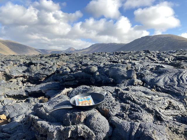 黒々とした溶岩の上に置かれたフライパンと、その中のソーセージ