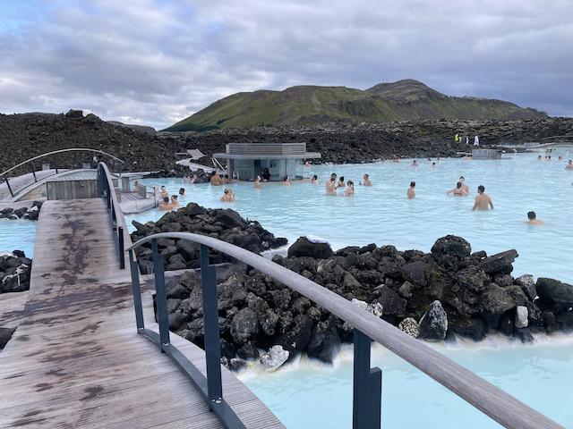 白く濁った水色のお湯で憩う、水着姿の人たち